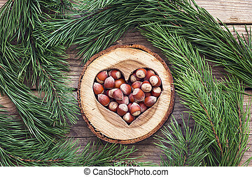 Hazelnut in a carved wooden heart and pine branches around on old wooden background.