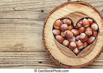 Hazelnut in a carved wooden heart on old wooden background. Top view.