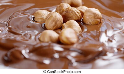 hazelnuts falling in melted chocolate