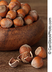 Hazelnuts in a wooden bowl on a table.