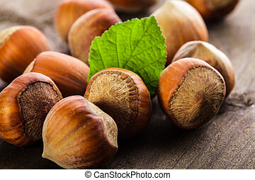 Hazelnuts with shell and green leaf on the wooden table