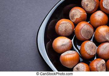 Hazelnuts in a black plate