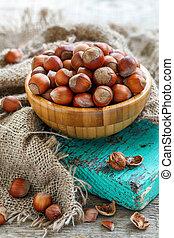 Hazelnuts in a bowl on old green board.