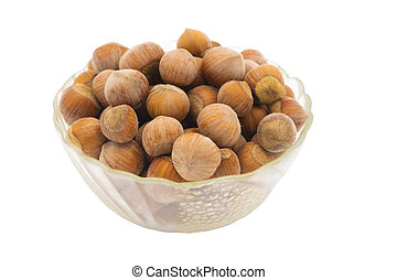 Hazelnuts in a glass vase. on white background.