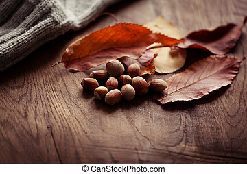 Hazelnuts with autumn leaves on the background of a wooden table
