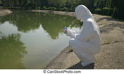 Hazmat biochemist shaking blue sample observing the chemical reaction standing near a contaminated lake