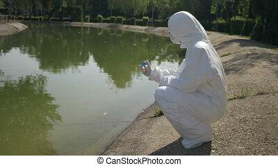 Hazmat biochemist shaking blue sample observing the chemical...