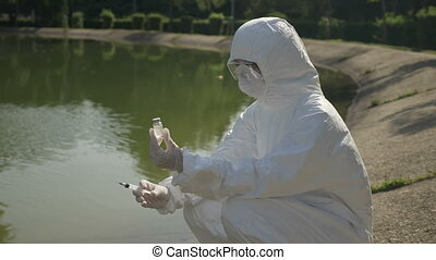 Hazmat biologist injecting a catalyst in a polluted water ...