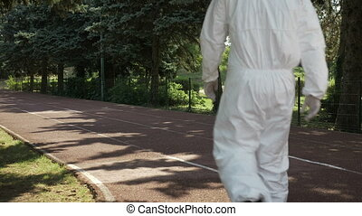 Hazmat technicians team walking on a an alley in public park...