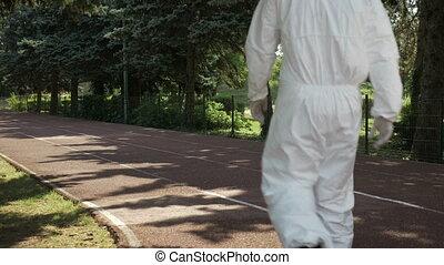 Hazmat technicians team walking on a an alley in public park...