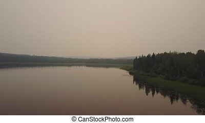 Hazy lake during dangerous forest fires in Alberta and British Columbia, Canada