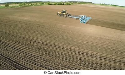 HD aerial footage of a modern tractor plowing dry field, preparing land for sowing