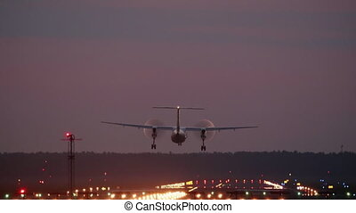 HD - Turboprop aircraft landing at night on runway