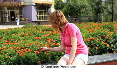 HD Young girl looking at marigold flowers