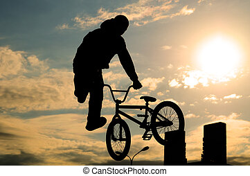 bicyclist - he bicyclist on a bicycle in a jump, on a...