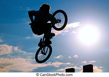 bicyclist - he bicyclist on a bicycle in a jump, on a ...