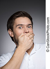 He? got a secret. Portrait of surprised young men covering his mouth by hand while standing isolated on grey