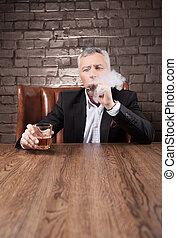 He is a boss. Bossy mature man in suit smoking a cigar and drinking whiskey