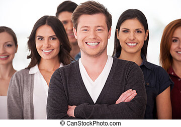 He is a real team leader. Confident young man keeping arms crossed and smiling while group of people standing on background