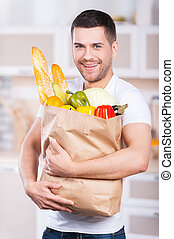 He is passionate about healthy food. Happy young man holding shopping bag full of groceries while standing in the kitchen