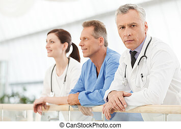 He is the most experienced and talented doctor. Confident mature doctors looking at camera while standing near his colleagues