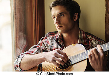 He loves the guitar sounds. Handsome young man sitting on the windowsill and playing guitar
