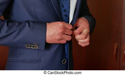 he man is putting on a blue suit. Morning businessman