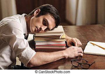 He needs a break. Handsome young author sleeping on the book stack