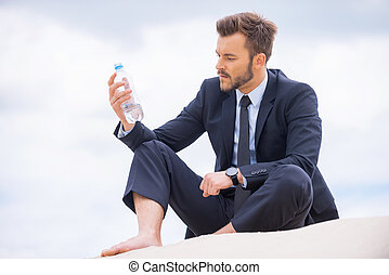 He needs to get refreshed. Depressed young businessman holding bottle with water and looking at it while sitting on sand