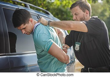 Shot of a policeman handcuffing a young driver