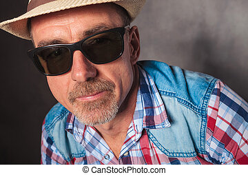head and shoulders of mature man wearing hat and sunglasses...