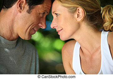Head and shoulders of mature romantic couple looking at each...