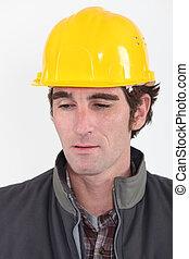 head and shoulders portrait of pensive craftsman