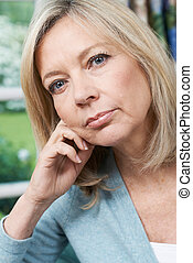 Head And Shoulders Portrait Of Thoughtful Mature Woman At...