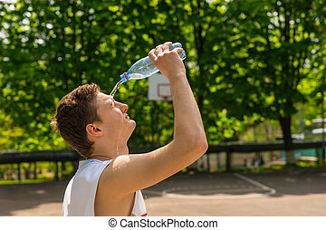 Head and Shoulders View of Young Athletic Man Pouring Water from Bottle onto Face, Taking a Break for Refreshment and Hydration on Basketball Court