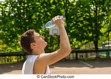 Athletic Man Pouring Water from Bottle onto Face