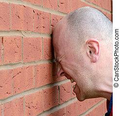 head banging - a man banging his head agaist the wall in...