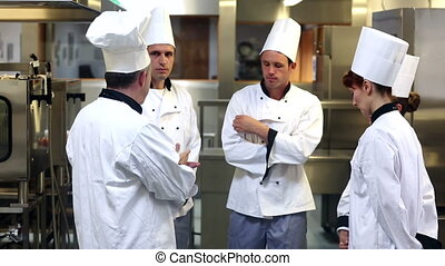 Head chef giving orders to his team in a commercial kitchen