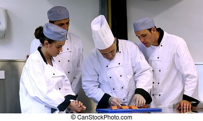 Head chef showing his trainees how to fillet a salmon in a...