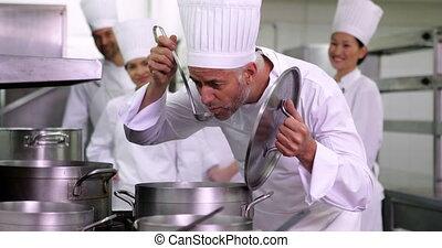 Head chef tasting pot of soup - Head chef tasting pot of...