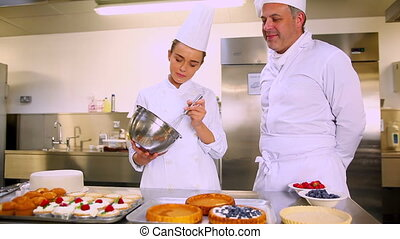 Head chef teaching his student how