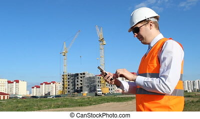 Head inspector in black glasses chewing gum and climbing in the phone on the background of building a house