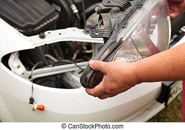 Head lights repair. Mechanic holding a new spare part