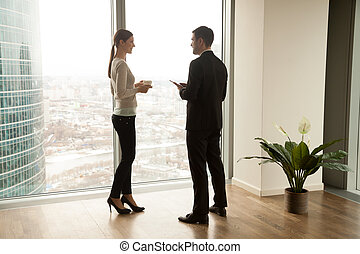 Businessman with tablet and young woman with cup of coffee standing together near large window with city view outside. Female and male coworkers pleasantly conversing during coffee break in office
