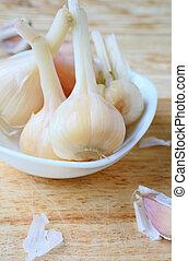 head marinated garlic in white bowl