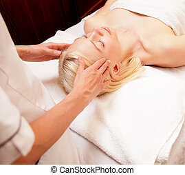 Head Massage - A tranquil woman receiving a head massage at...