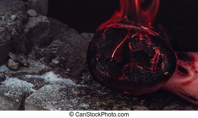 Head of a dummy burns on the stone earth. Close up video.