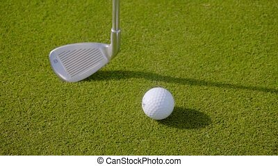 Head of a golf club with a white golf ball on a neatly...