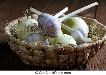 head of garlic and onions in a wicker basket