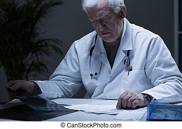 Head of hospital ward reading medical records